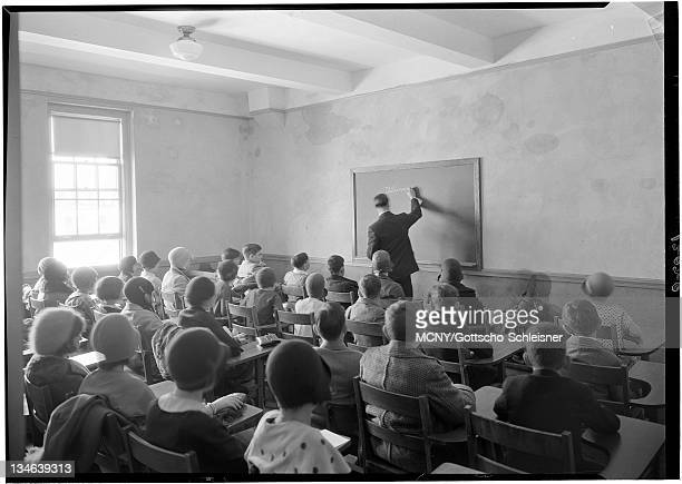 Classroom full of children seated and teacher writing on chalkboard. Located at Garfield Place and 8th Avenue, Brooklyn, N.Y.