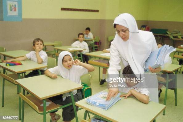 Classroom of a Islamic school Teacher gives books of texts