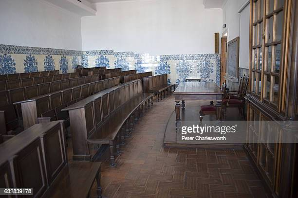 A classroom or lecture hall with traditional ceramic tiles lining the walls and wooden benches a the Old University of Coimbra The public university...