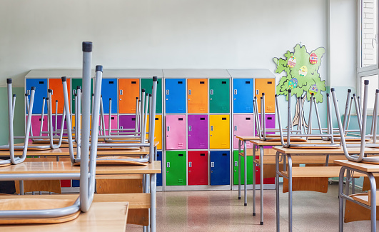 Classroom with colorful lockers and raised chairs on the tables 1015350772