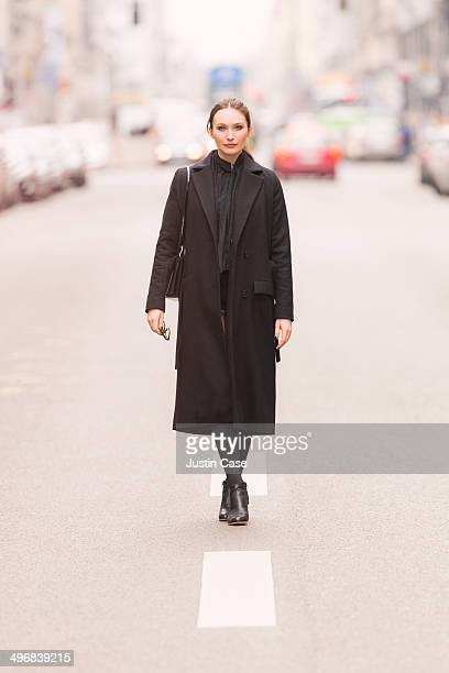 classy business woman standing on a city road - black coat stock pictures, royalty-free photos & images