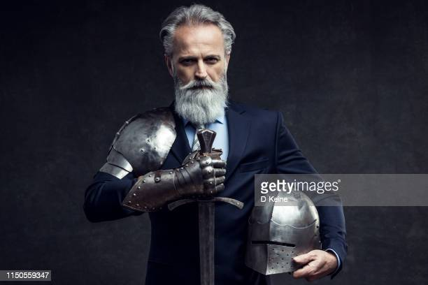 classy dressed senior businessman with knight sword - protezione foto e immagini stock