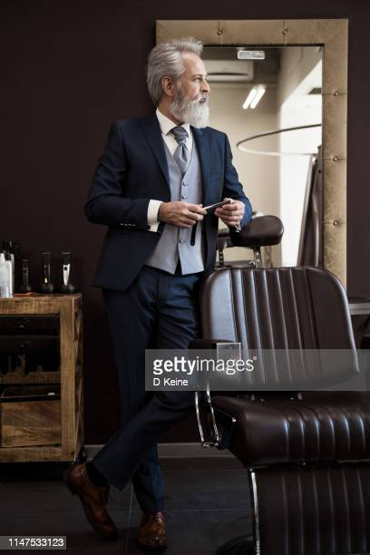classy dressed senior man in barber shop - coat stock pictures, royalty-free photos & images