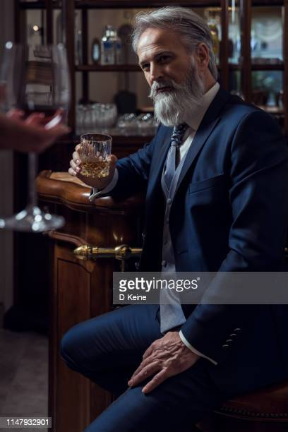 classy dressed senior man sitting in bar - metrosexual stock pictures, royalty-free photos & images