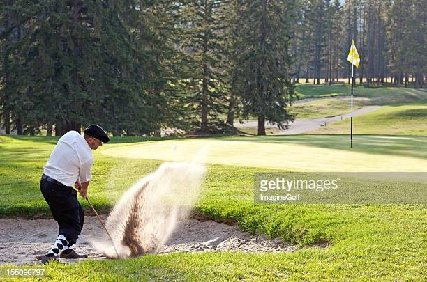 classy male caucasian golfer hitting bunker shot - plus fours stock photos and pictures