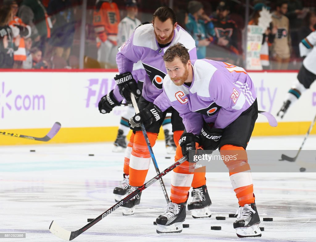 Claude Giroux #28 and Sean Couturier #14 of the Philadelphia Flyers along with the rest of their teammates wear special jerseys for warm-ups in honor of Hockey Fights Cancer Awareness night before their game against the San Jose Sharks on November 28, 2017 at Wells Fargo Center in Philadelphia, Pennsylvania.