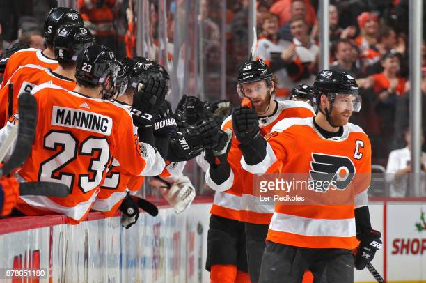 Claude Giroux and Sean Couturier of the Philadelphia Flyers celebrate Couturier's second period goal against the New York Islanders with their...