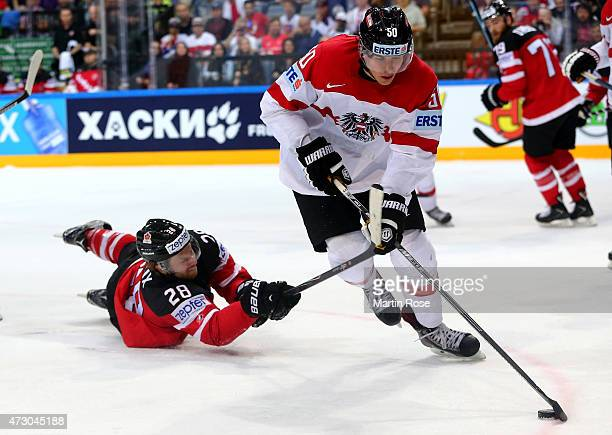 Claude Giroux of Canada and Mario Fischer of Austria battle for the puck during the IIHF World Championship group A match between Canada and Austria...