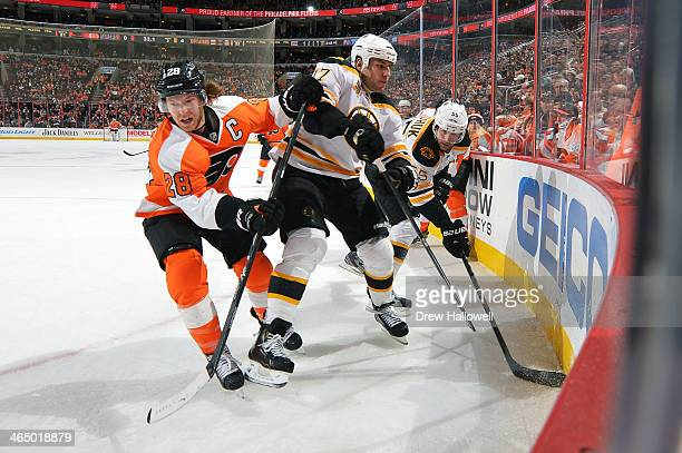 Claude Giroux of the Philadelphia Flyers battles for the puck against Milan Lucic and Johnny Boychuk of the Boston Bruins at the Wells Fargo Center...