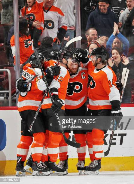 Claude Giroux of the Philadelphia Flyers celebrates his third period goal against the Carolina Hurricanes with Shayne Gostisbehere Michael Raffl and...