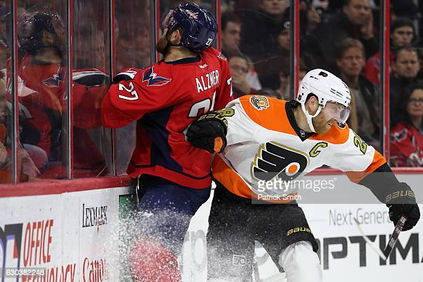 Claude Giroux of the Philadelphia Flyers checks Karl Alzner of the Washington Capitals during the second period at Wells Fargo Center on December 21...