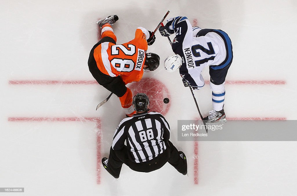 Claude Giroux #28 of the Philadelphia Flyers faces off with Olli Jokinen #12 of the Winnipeg Jets on February 23, 2013 at the Wells Fargo Center in Philadelphia, Pennsylvania. The Flyers went on to defeat the Jets 5-3.