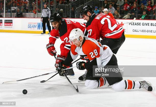Claude Giroux of the Philadelphia Flyers falls to the ice battling for the puck against Mike Mottau and Mark Fraser of the New Jersey Devils at the...