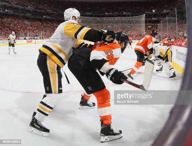 Claude Giroux of the Philadelphia Flyers gets the high stick from Olli Maatta of the Pittsburgh Penguins during the second period in Game Three of...