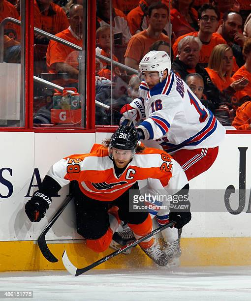 Claude Giroux of the Philadelphia Flyers is checked by Derick Brassard of the New York Rangers during the first period in Game Three of the First...