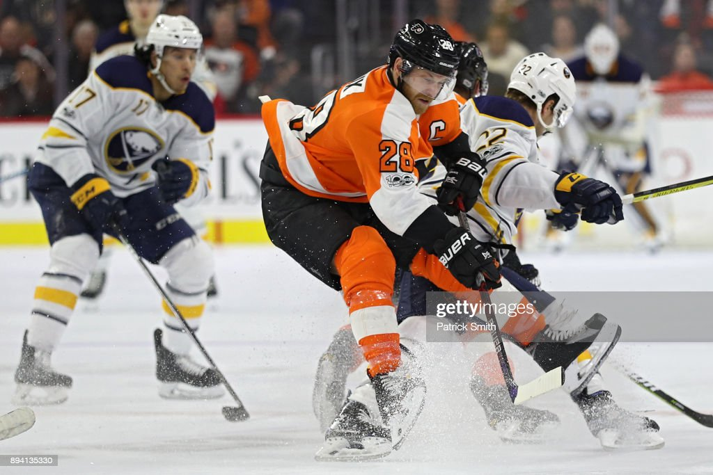 Claude Giroux #28 of the Philadelphia Flyers is checked by Johan Larsson #22 of the Buffalo Sabres during the third period at Wells Fargo Center on December 14, 2017 in Philadelphia, Pennsylvania.