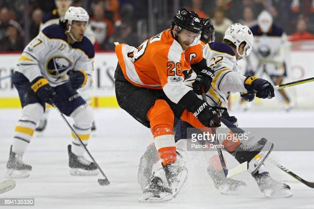 Claude Giroux of the Philadelphia Flyers is checked by Johan Larsson of the Buffalo Sabres during the third period at Wells Fargo Center on December...