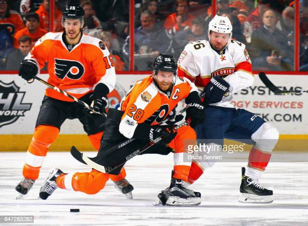 Claude Giroux of the Philadelphia Flyers is checked by Thomas Vanek of the Florida Panthers during the second period at the Wells Fargo Center on...