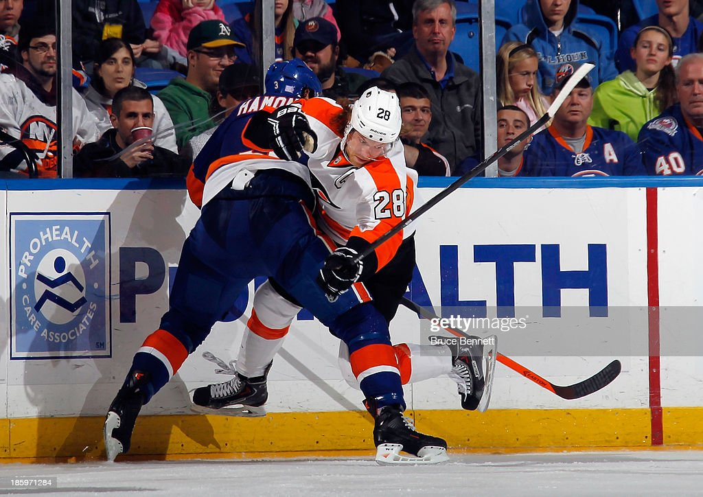 Claude Giroux #28 of the Philadelphia Flyers is checked by Travis Hamonic #3 of the New York Islanders at the Nassau Veterans Memorial Coliseum on October 26, 2013 in Uniondale, New York.
