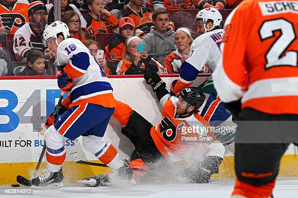Claude Giroux of the Philadelphia Flyers is hit by Frans Nielsen and Ryan Strome of the New York Islanders in the third period at Wells Fargo Center...