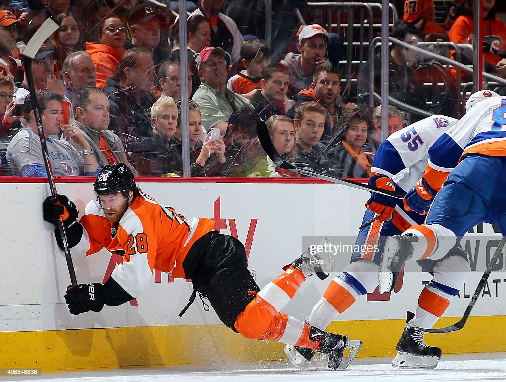 Claude Giroux #28 of the Philadelphia Flyers is tripped up by Johnny Boychuk #55 of the New York Islanders in the first period on April 7, 2015 at the Wells Fargo Center in Philadelphia, Pennsylvania.