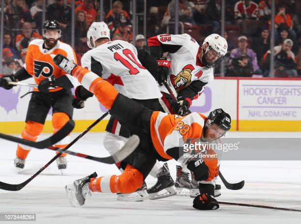Claude Giroux of the Philadelphia Flyers is tripped up by Tom Pyatt of the Ottawa Senators during the second period at the Wells Fargo Center on...