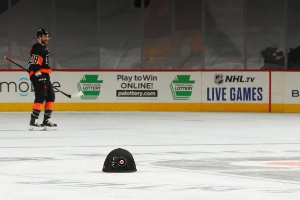 Claude Giroux of the Philadelphia Flyers looks on as a giant hat thrown by mascot Gritty of the Philadelphia Flyers rests on the ice after a hat...