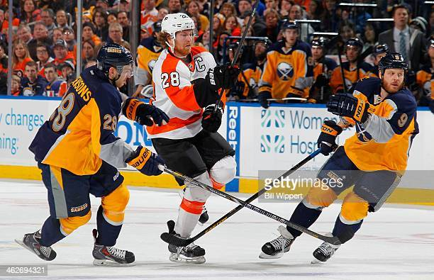 Claude Giroux of the Philadelphia Flyers looks to jump between Zemgus Girgensons and Steve Ott of the Buffalo Sabres on January 14 2014 at the First...
