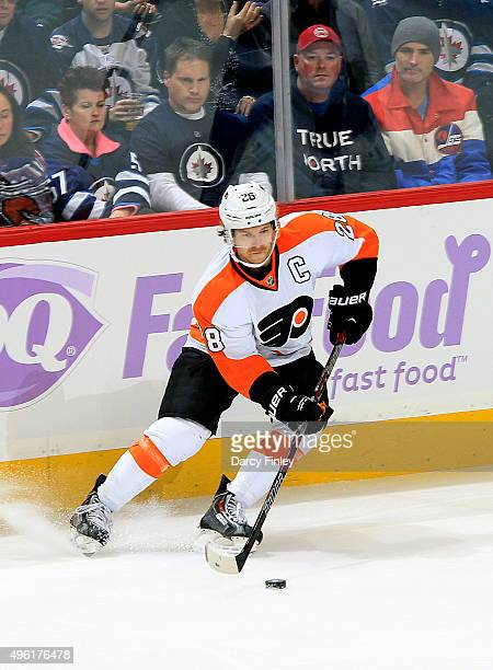 Claude Giroux of the Philadelphia Flyers plays the puck along the boards during first period action against the Winnipeg Jets at the MTS Centre on...