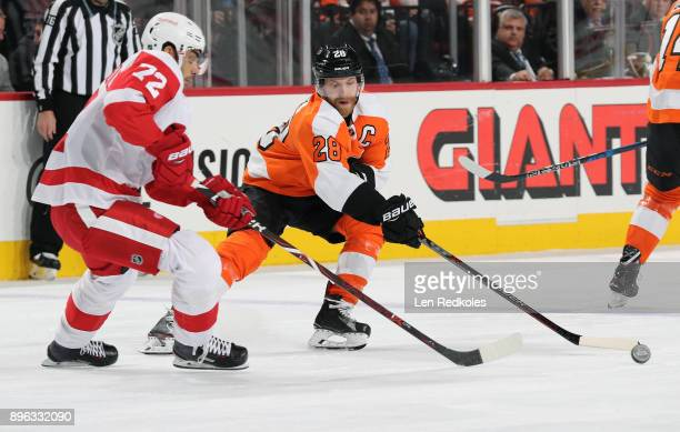 Claude Giroux of the Philadelphia Flyers reaches to play the loose puck against Andreas Athanasiou of the Detroit Red Wings on December 20 2017 at...