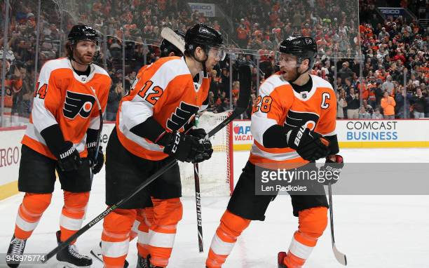 Claude Giroux of the Philadelphia Flyers reacts with teammates Michael Raffl and Sean Couturier following a second period goal against the Carolina...