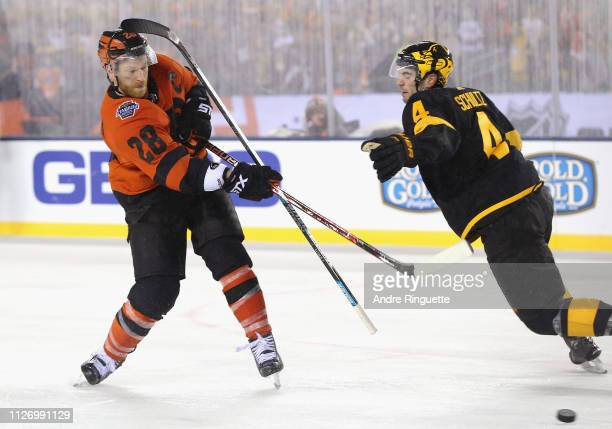 Claude Giroux of the Philadelphia Flyers shoots and scores the gamewinning goal as Justin Schultz of the Pittsburgh Penguins loses control of his...