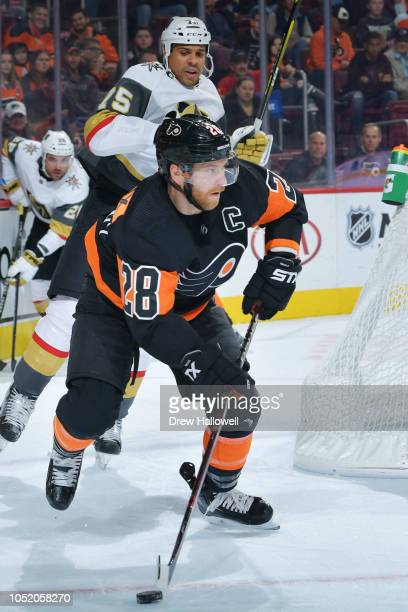Claude Giroux of the Philadelphia Flyers skates with the puck away from Ryan Reaves of the Vegas Golden Knights at the Wells Fargo Center on October...