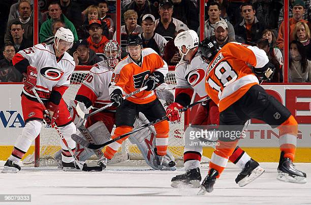 Claude Giroux of the Philadelphia Flyers tries to tip a shot from teammate Mike Richards as Cam Ward and Joni Pitkanen of the Carolina Hurricanes...