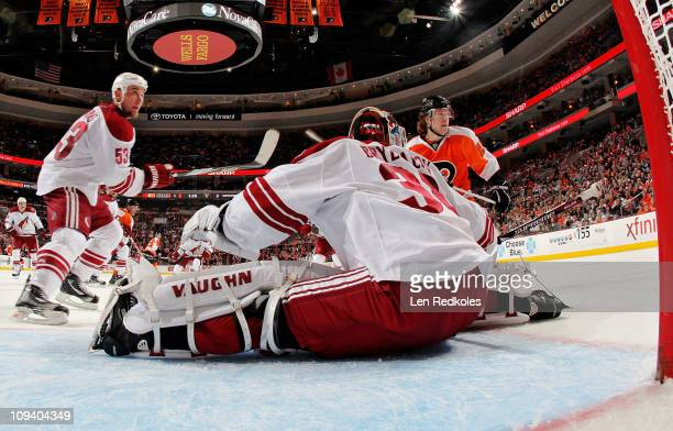 Claude Giroux of the Philadelphia Flyers waits to slap a shot on goal against Derek Morris and Ilya Bryzgalov of the Phoenix Coyotes on February 22...