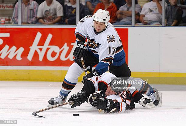 Claude Lapointe of the Philadelphia Flyers is tripped up by John Gruden of the Washington Capitals during the game at John Labatt Centre on September...