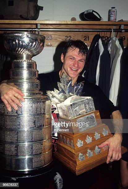 Claude Lemieux of the New Jersey Devils celebrates with the Stanley Cup and the Conn Smythe Trophy after winning 1995 Stanley Cup playoffs against...