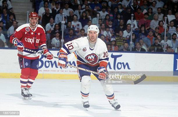 Claude Loiselle of the New York Islanders skates on the ice as Todd Krygier of the Washington Capitals follows behind during the 1993 Division Semi...