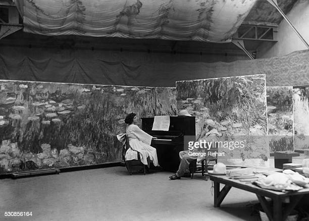 Claude Monet French painter is shown seated in his studio at Giverny A woman plays a piano near him Undated photograph