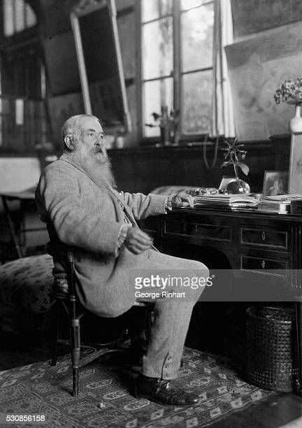 Claude Monet is shown in his home in Giverny France He is shown seated at a desk Undated