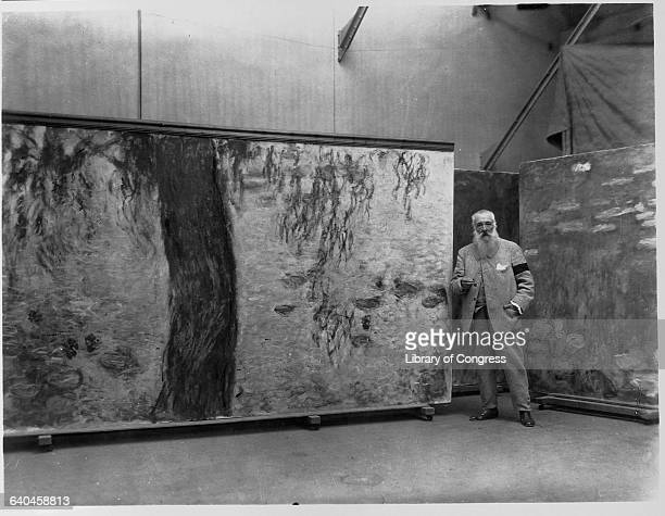 Claude Monet standing in his studio with a panel of his Nympheas mural | Located in Musee de l'Orangerie