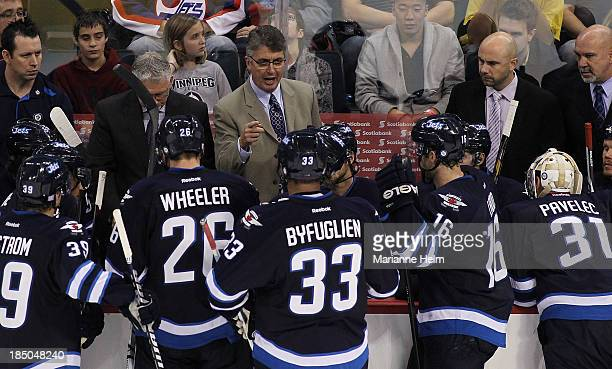Claude Noel head coach of the Winnipeg Jets talks to his team from the bench in third period action of an NHL game against the Dallas Stars at the...