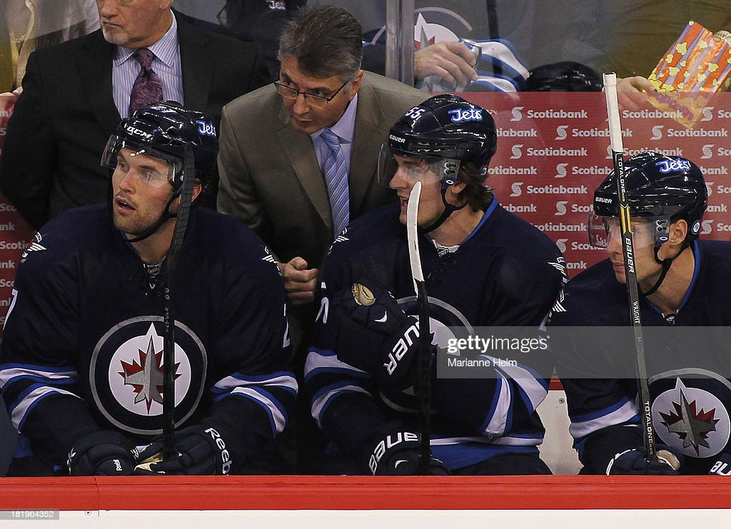 Claude Noel, head coach of the Winnipeg Jets, talks with Eric Tangradi #27, Mark Scheifele #55 and James Wright #17 on the bench in third period action during an NHL preseason game at the MTS Centre on September 26, 2013 in Winnipeg, Manitoba, Canada.
