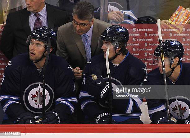 Claude Noel head coach of the Winnipeg Jets talks with Eric Tangradi Mark Scheifele and James Wright on the bench in third period action during an...