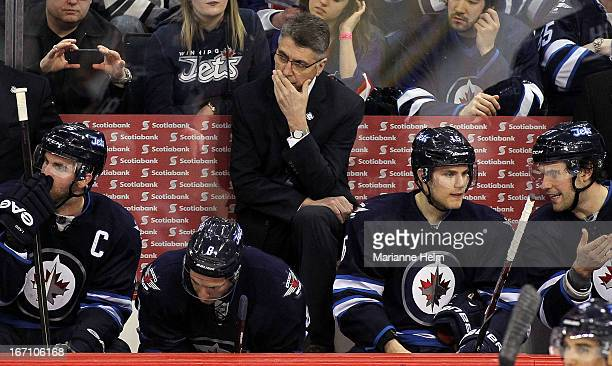 Claude Noel head coach of the Winnipeg Jets watches the play on the ice during third period action in a game against the New York Islanders on April...
