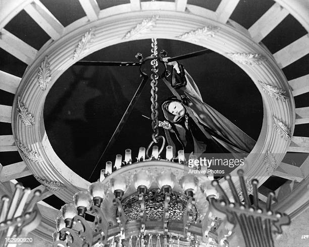 Claude Rains attempts to cut a chain holding a chandelier in a scene from the film 'Phantom Of The Opera' 1943