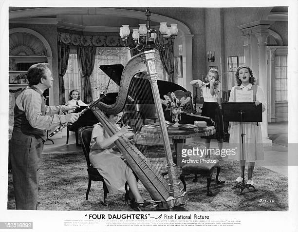 Claude Rains conducting Gale Page Rosemary Lane Priscilla Lane and Lola Lane in a scene from the film 'Four Daughters' 1938