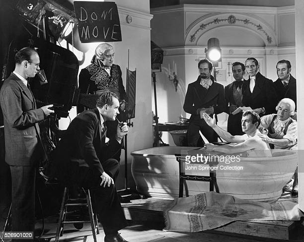 Claude Rains portraying Napoleon Bonaparte looks over to director Frank Borzage between scenes of the 1936 film Hearts Divided