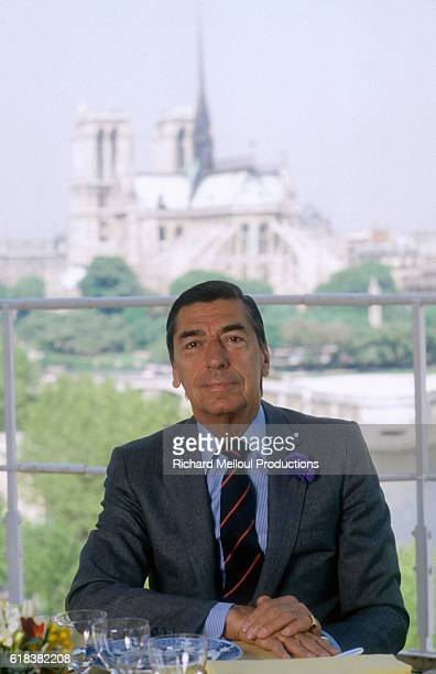 Claude Terrail sits at a dining table in his famous establishment The Cathedral of Notre Dame de Paris can be seen through the window behind him