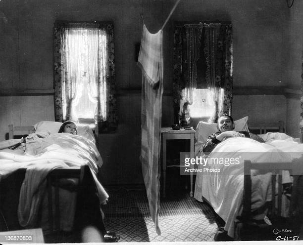 Claudette Colbert and Clark Gable each in a twin bed of their own in the same room with a curtain separating them in a scene from the film 'It...